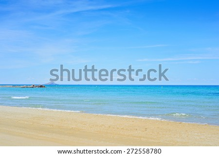 Sandy beach and blue Mediterranean sea and mountain on horizon - stock photo