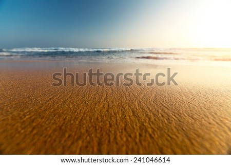 Sandy beach and blue sea with waves at sunset - stock photo