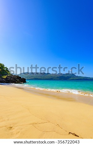 sandy beach and calm blue sea surf