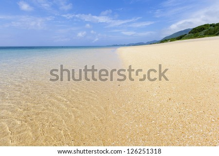 Sandy beach and clear turquoise waters on a tropical island. Selective focus on foreground beach. - stock photo