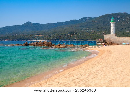 Sandy beach and lighthouse tower. Coastal landscape of Propriano town, Corsica island, France - stock photo