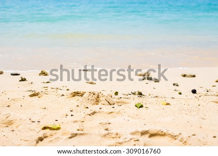 Sandy beach and soft wave of clear turquoise the sea (selective focus) - stock photo