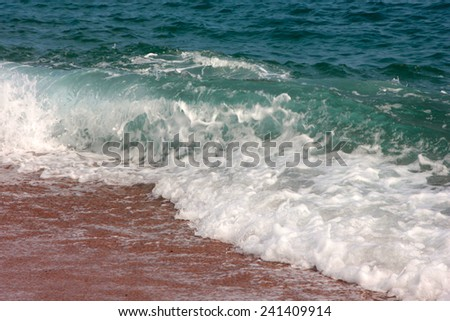 Sandy beach and the waves of the Mediterranean Sea - stock photo