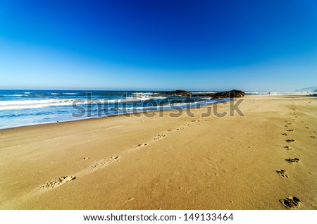 Sandy beach at Lincoln City, Oregon with footprints - stock photo