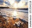 Sandy beach at sunset. Stormy sea - stock photo