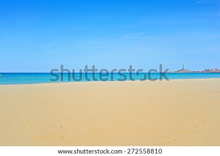 Sandy beach, blue Mediterranean sea and lighthouse on horizon - stock photo