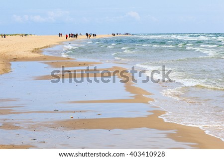 Sandy beach by the sea with people who walk - stock photo