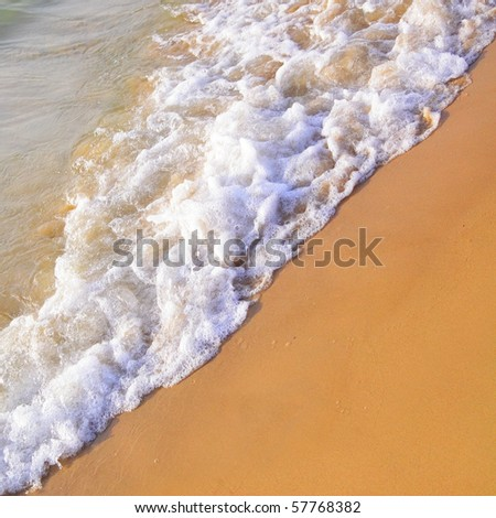 Sandy beach of seaside resort with clear water - stock photo