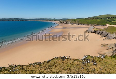 Sandy beach on the Gower Wales uk Pobbles beach next to Three Cliffs Bay in summer with blue sky and sea illustration