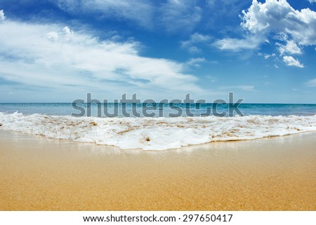 Sandy beach with blue cloudy sky and waves