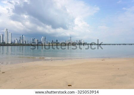 Sandy beach with the new highway over the bay and the skyscrapers of Panama city in background, Panama, Central America - stock photo