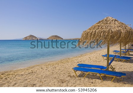 Sandy beach with umbrellas and sunbeds blue - found on any island in Greece and Europe - stock photo