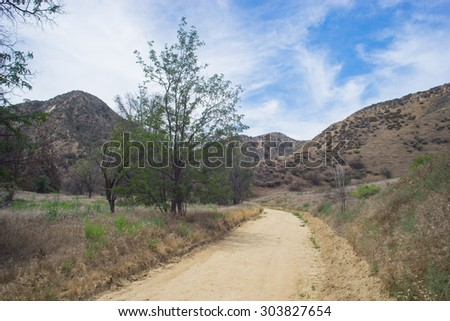 Sandy dirt trail leads into the desert wilderness of southern California. - stock photo