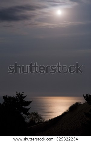 Sandy dunes with moon during nighttime. Baltic coast, Lithuania. - stock photo