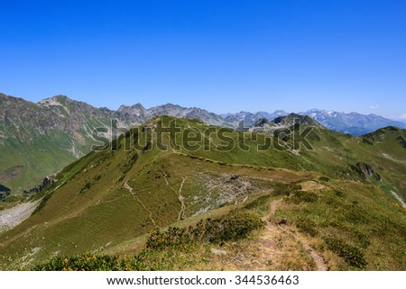 sandy footpath across the mountain range covered with green alpine meadows in Caucasus Mountains in Abkhazia Georgia