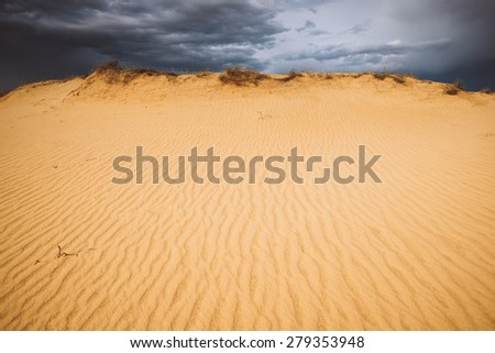 Sandy landscape in the desert, the dark clouds and yellow sand - stock photo