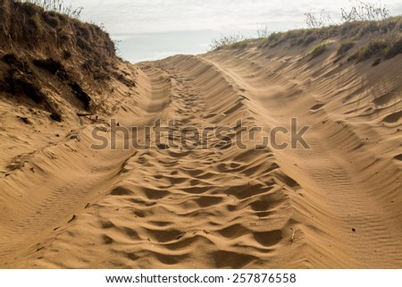 Sandy road and track over the sand dunes in Kauai with tire tracks - stock photo