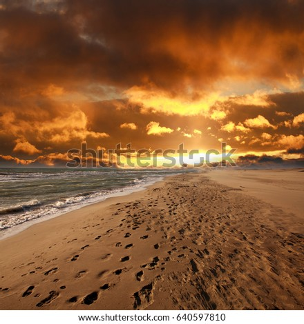 Sandy sea beach with footprints on the background of dramatic sky cloud