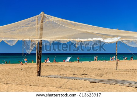 Sandy seashore with fishing nets used as decorations. Beautiful sunny blue sky landscape. Anapa resort on Black Sea coast. People resting on the beach by the shoreline.