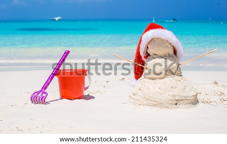 Sandy snowman with red Santa Hat and beach toys - stock photo
