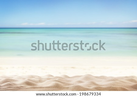 Sandy summer beach with blur sea on background - stock photo