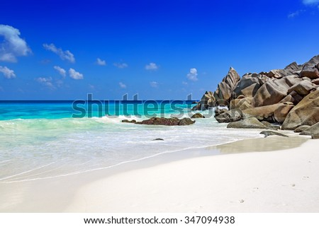 Sandy tropical beach of La Digue island Seychelles with typical rocks in turquoise ocean.   - stock photo
