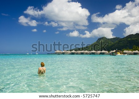 Sandy tropical beach with bungalows and woman in foreground