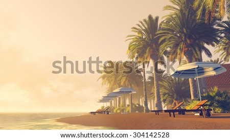 Sandy tropical beach with palm trees, deckchairs and parasols at sunrise or sunset - stock photo