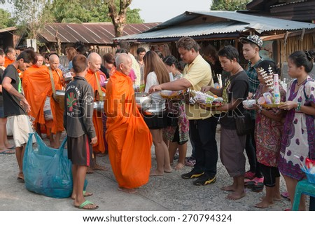 Sangkhlaburi,Thailand-14 April 2015::Give alms to a Buddhist monk Buddhist Monks for alms at the Mon village, on 14 April 2015 in Sangkhlaburi,Thailand - stock photo
