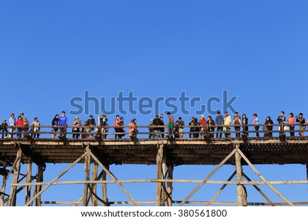 Sangkhlaburi, Thailand - February 14, 2016: Crowd of tourist are enjoying on wooden bridge against clear blue sky.