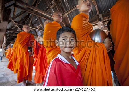 Sangkla Buri , Kanchanaburi, THAILAND - OCT 30 : Buddhist monks are given food offering from people for End of Buddhist Lent Day. on October 30, 2012 in Sangkla Buri,Kanchanaburi,T hailand.