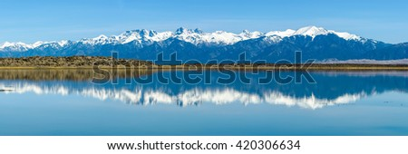 Sangre de Cristo Mountains - Panoramic view of Snow-capped Sangre de Cristo Mountains, including 14ers: Challenger Point, Kit Carson Peak, Crestone Peak, Crestone Needle, reflecting in San Luis Lake.  - stock photo