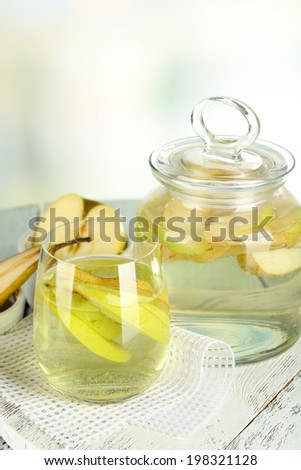 Sangria drink in glass and jar on wooden table, on light background - stock photo