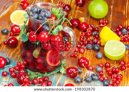 Sangria Fruit Punch. Refreshing fruit punch beverage in pitcher over rustic wooden background. - stock photo