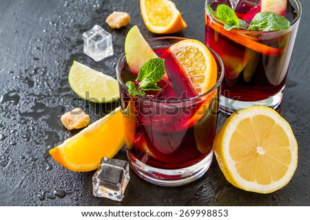 Sangria in glasses with ingredients - orange, lemon and lime slices, sugar, dark stone background
