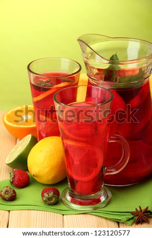 sangria in jar and glasses with fruits, on wooden table, on green background