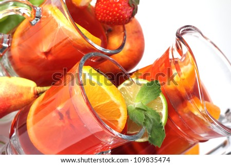 Sangria summer wine in pitcher and glasses and fruits isolated on white - stock photo
