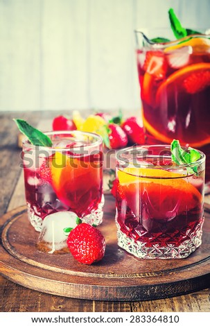 Sangria with fresh strawberries, oranges, mint and ice served in glasses standing on rustic wooden background. Cold and refreshing summer drink. Toned. Selective focus on front glass. - stock photo