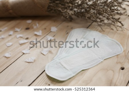 Sanitary pads and dry flower on the wooden background. Woman hygiene protection