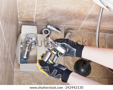 Sanitary technician replaces plumbing trap of sink in bathroom - stock photo