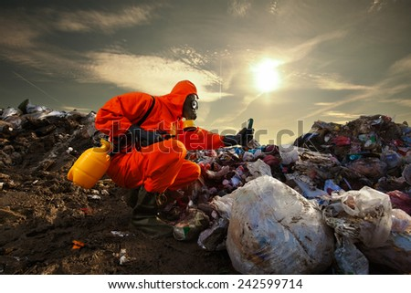 Sanitation worker measuring pollution on the landfill - stock photo