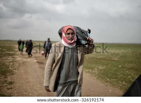 SANL?URFA,TURKEY, 18 FEBRUARY 2015 Syrian refugees walking on Turkey-Syria border in Suruc district. - stock photo