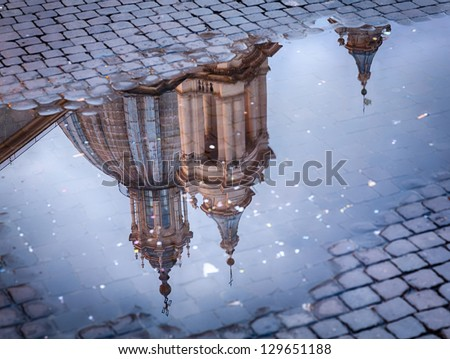 Sant Agnese in Agone lit up by setting sun in Piazza Navona reflected in puddle - stock photo