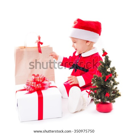 Santa baby girl with gift box and christmas decorations on white - stock photo