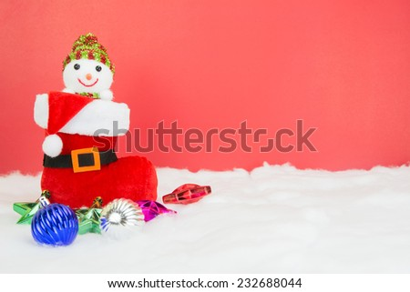 Santa boots and Christmas balls with snowman on white snow on red background, concept christmas - stock photo
