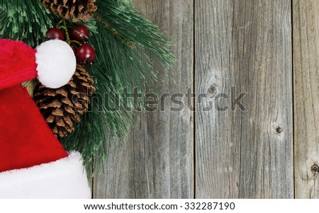 Santa cap and evergreen branch with pine cones on rustic wood. Christmas concept in horizontal layout.  - stock photo