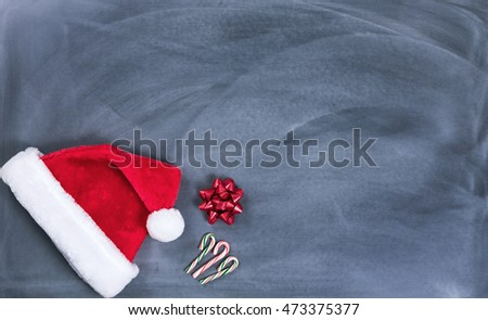 Santa cap, gift bow and candy canes on erased chalkboard for Christmas wish list concept.