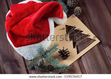 Santa cap, xmas card, fir-tree branches and cones, studio shot