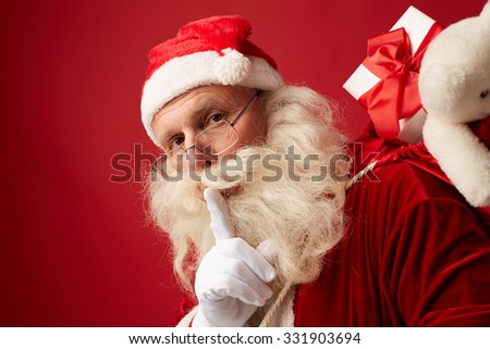 Santa carrying sack with xmas gifts - stock photo