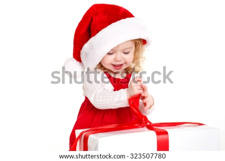 Santa child with christmas gifts isolated on white. Cute little girl in the santa claus hat. Child holding Christmas gift box in hand. Isolated on white background - stock photo